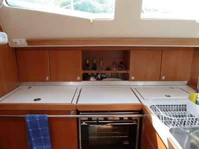 Galley features 3-burner stovetop & oven, 2 top-loading freezer/fridges and dbl sink