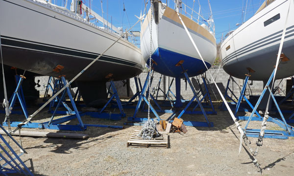 Sailboat in storage cradle secured by tensioned webbing tie-downs to ground anchors