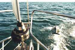 dolphin leaping ahead of a sailboat during a crossing of the Bay of Biscay